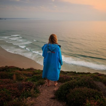 Standing on cliff top in sky blue Dryrobe